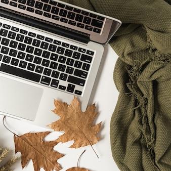 Home office tisch schreibtisch arbeitsbereich mit laptop, trockenem herbstlaub und decke. flache lage, draufsicht.