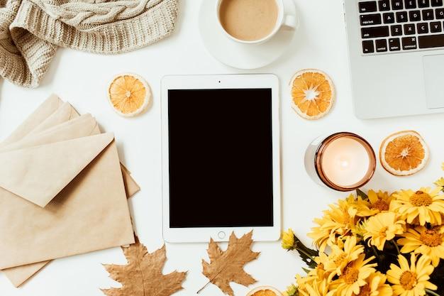 Home office tisch schreibtisch arbeitsbereich mit leerem bildschirm tablet mit kopierraum. gelber gänseblümchenblumenstrauß, orangenscheiben. flache lage, draufsicht