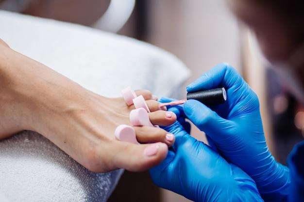 Home salon pediküre fußpflege und nagel der prozess der professionellen pediküre master in blauen handschuhen tragen hellrosa gelpolitur auf