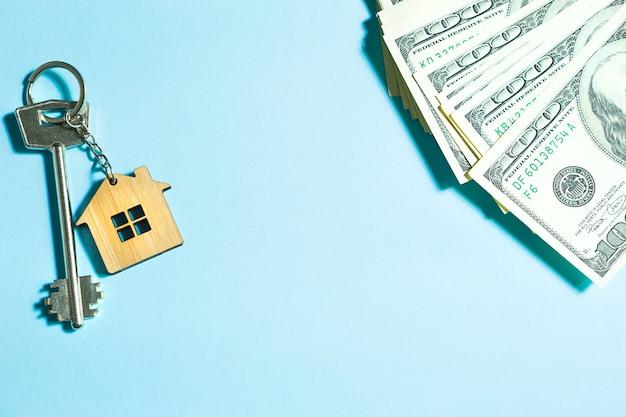 Home-schlüssel mit einem schlüsselbund auf einem stapel von 100-dollar-scheinen auf blauem hintergrund. kauf einer wohnung, eines hauses, einer immobilie, eines geschäfts-, hypotheken- und wohnungsdarlehens von einer bank, ersparnisse, bargeld, umzug. platz kopieren