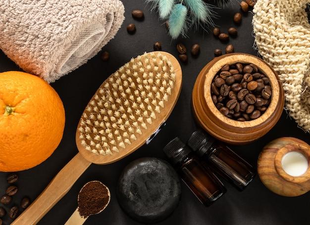 Home spa-konzept. körperbürste, seife, handtuch, orangen, kaffeebohnen und ätherisches öl für die anti-cellulite-massage und hautbehandlung an der schwarzen wand. flaches lay-design