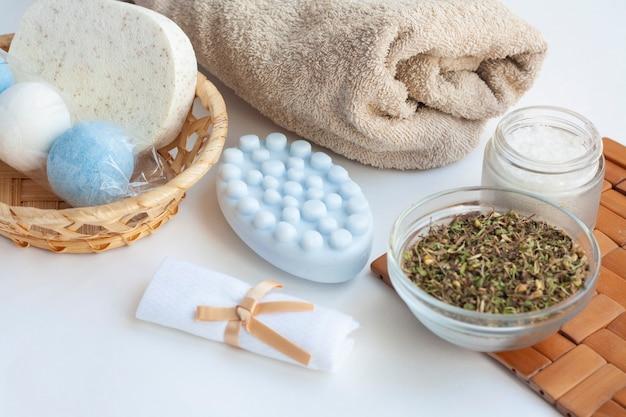 Home spa salon, kosmetik, seife, schwamm, handtuch, badesalz und trockene kräuter