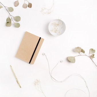 Homeoffice-schreibtisch mit handwerkstagebuch, stift, kopfhörern und eukalyptuszweigen auf weißem hintergrund. flache lage, ansicht von oben