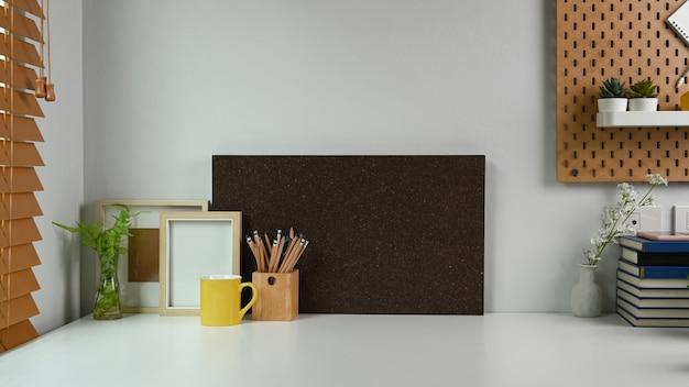 Homeoffice-schreibtisch mit leerem rahmen, bleistifthalter, kaffeetasse und zimmerpflanze.