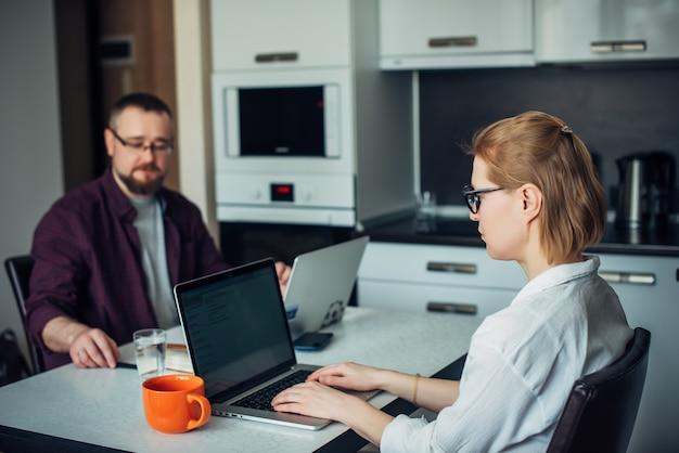 Homeoffice während der selbstisolation. mann und frau sitzen an einem tisch in der küche, arbeiten aus der ferne an laptops zusammen und diskutieren geschäftliche themen. seitenansicht. konzentrieren sie sich auf die frau in der brille.