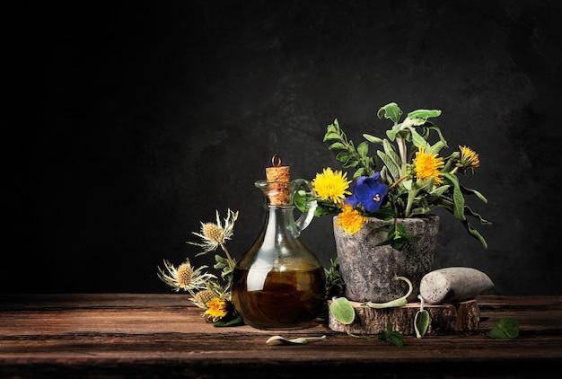 Homöopathie und alternativmedizin. kochen. heilkräuter in steinmörser und ätherisches öl in glasflaschen. zerkleinerte heilkräuter auf holztisch.