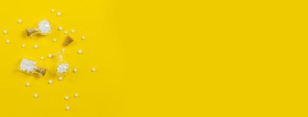 Homöopathische glasflasche auf gelbem grund. alternative kräutermedizin homöopathie, gesundheitskonzept health