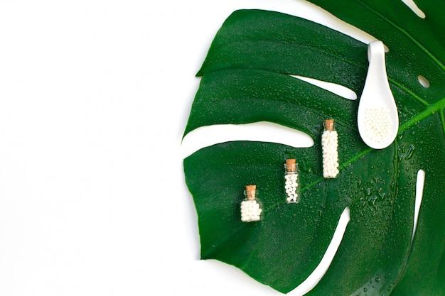 Homöopathische kügelchen in drei glasflaschen auf nassem palmblatthintergrund.