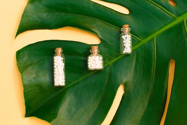 Homöopathische kügelchen in drei glasflaschen auf palmblatthintergrund.