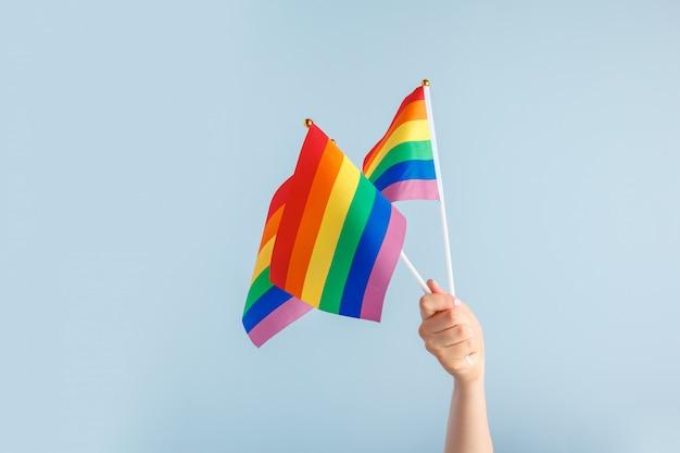 Homosexuell flaggen in frauenhand auf grauem hintergrund