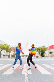 Homosexuell mit der regenbogenflagge, die auf straße begegnet