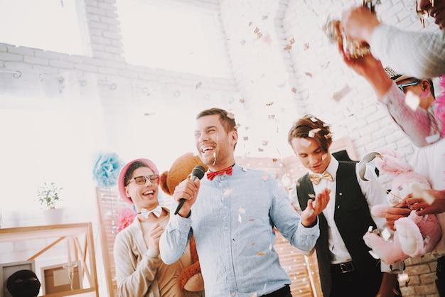 Homosexuelle feiern zu hause eine party und singen ins mikrofon