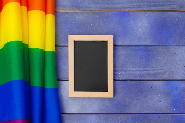 Homosexuelle flagge des hellen regenbogens auf hölzerner und leerstelle