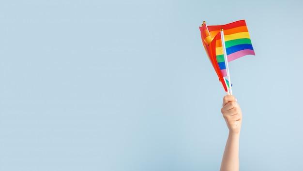 Homosexuelle flaggen in der hand der frauen auf grau