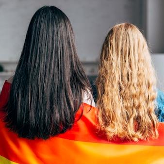 Homosexuelle frauen, die in der regenbogenflagge bedecken