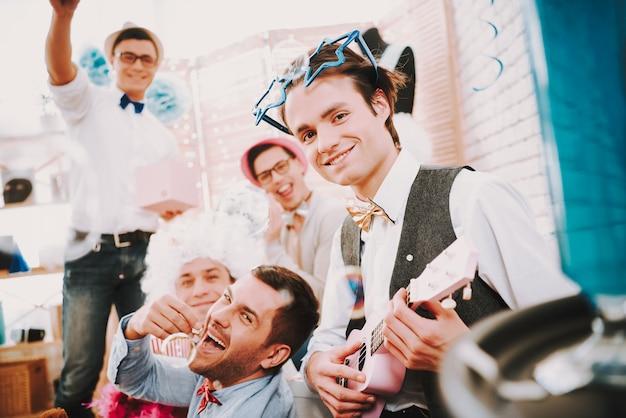 Homosexuelle kerle des lächelns in den fliegen, die zusammen auf couch an der party aufwerfen