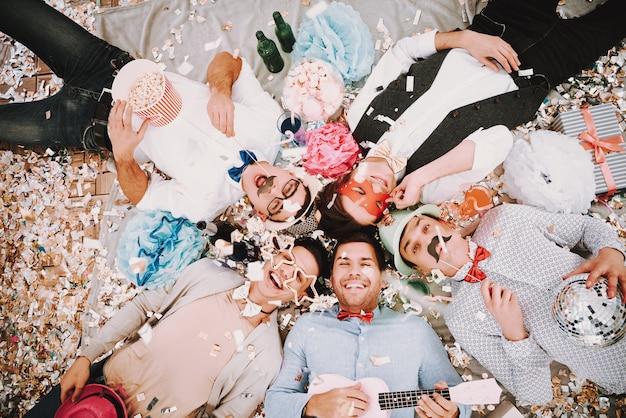 Homosexuelle kerle, die im kreis mit konfettis an der party liegen.