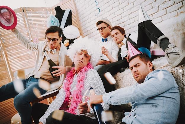 Homosexuelle kerle in den fliegen, die auf couch nach party sich entspannen.