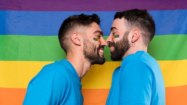 Homosexuelle männer auf lgbt-regenbogenflagge von angesicht zu angesicht