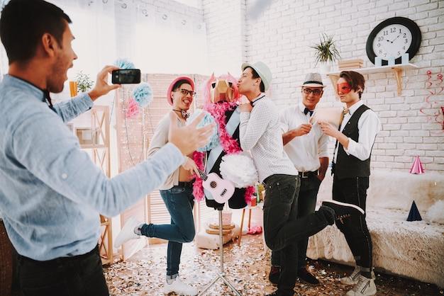 Homosexuelle männer, die selfie am telefon an der partei nehmen.