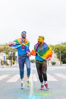 Homosexuelle männer in mehrfarbigem pulver, die spaß auf der straße haben