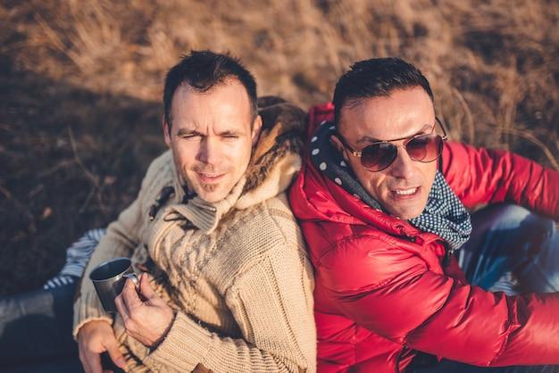 Homosexuelle männliche paare, die auf decke im gras legen