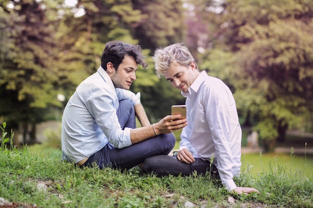 Homosexuelle paare, die einen smartphone im park überprüfen
