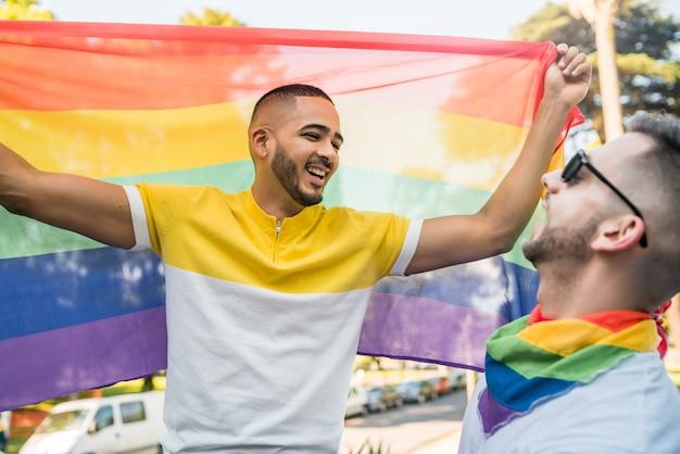 Homosexuelle paare, die ihre liebe mit regenbogenflagge umfassen und zeigen.