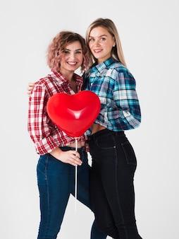 Homosexuelle paare, die mit ballon für valentinsgrüße aufwerfen