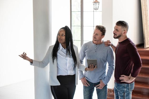 Homosexuelle paare mit weiblicher immobilienagentur des afroamerikaners im neuen haus