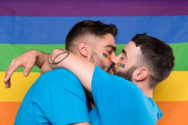 Homosexuelle paare von männern, die auf regenbogenflagge umarmen und küssen