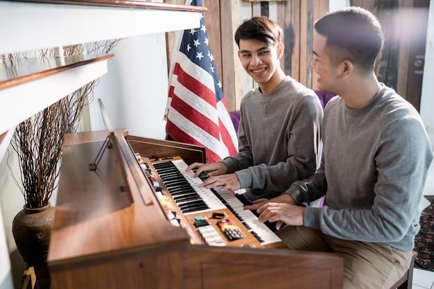 Homosexueller lgbt-mann spielt klavier. zum glück mit seiner geliebten