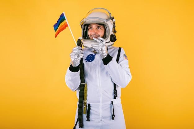 Homosexueller männlicher kosmonaut im raumanzug und im helm, der lgtbi regenbogenfahne auf gelber wand hält.