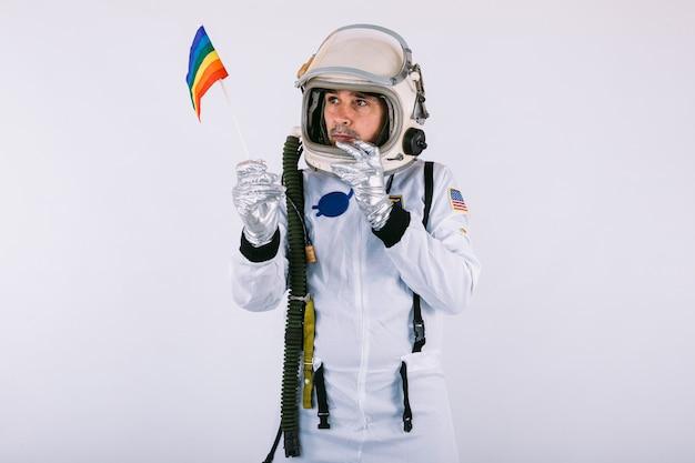 Homosexueller männlicher kosmonaut im raumanzug und im helm, lgtbi regenbogenfahne haltend, auf weißem hintergrund.
