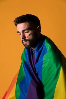 Homosexueller mann eingewickelt in der lgbt-regenbogenflagge