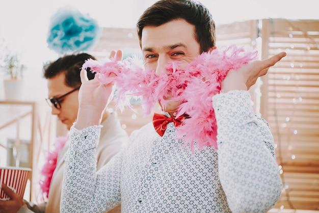 Homosexueller mann mit fliege und mit federboa an der party