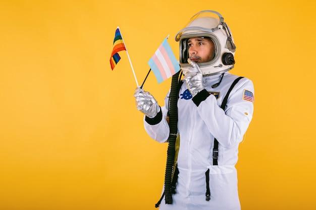 Homosexueller transsexueller männlicher kosmonaut mit ernster geste im raumanzug und im helm, die lgtbi regenbogenfahne und transgenderfahne auf gelber wand halten.
