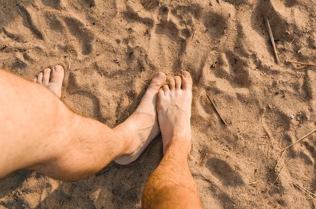 Homosexuelles beziehungskonzept. männlicher haariger fuß, der anderen männlichen fuß am strand berührt, draufsicht. versteckte berührungen beim entspannen draußen.