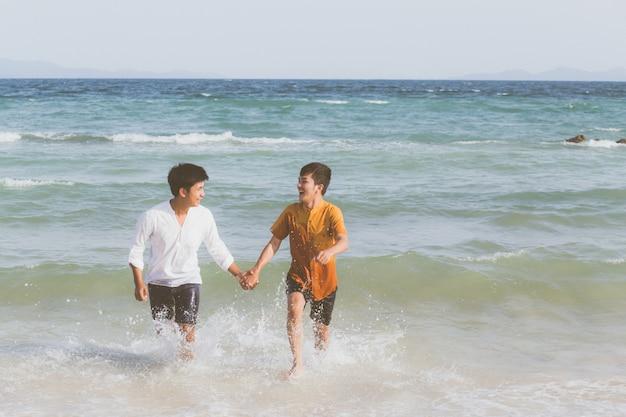 Homosexuelles junges asiatisches paar, das mit fröhlich zusammen läuft