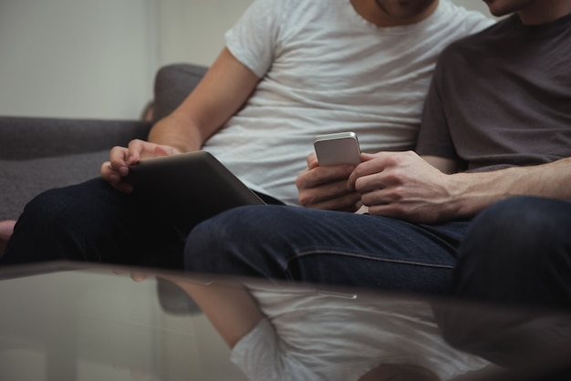 Homosexuelles paar, das auf sofa sitzt und digitale tablette betrachtet