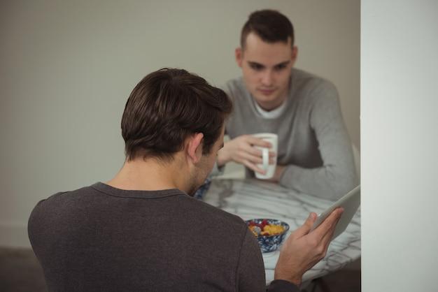 Homosexuelles paar, das digitale tablette beim frühstück betrachtet