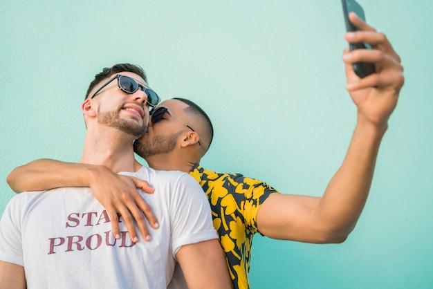 Homosexuelles paar, das ein selfie mit handy nimmt.