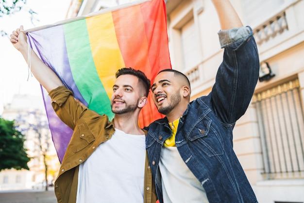 Homosexuelles paar, das ihre liebe mit regenbogenfahne umarmt und zeigt.