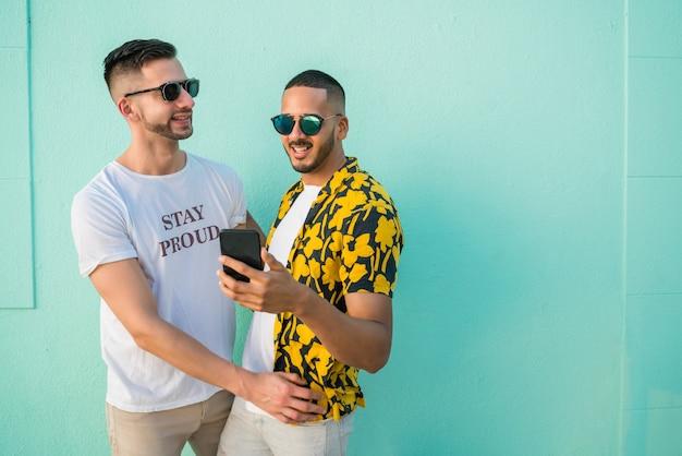 Homosexuelles paar, das zeit zusammen verbringt, während es telefon benutzt.