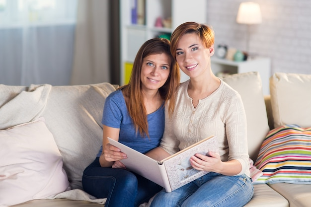 Homosexuelles paar lesbischer frauen zu hause auf der couch und schaut sich ein buch oder ein fotoalbum an
