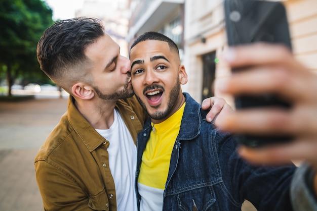 Homosexuelles paar macht ein selfie auf der straße