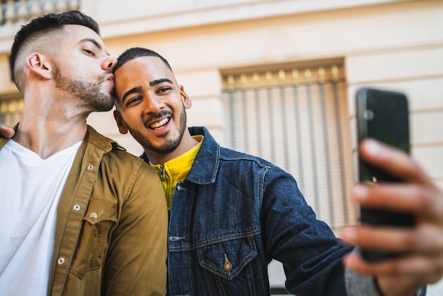 Homosexuelles paar macht ein selfie auf der straße.