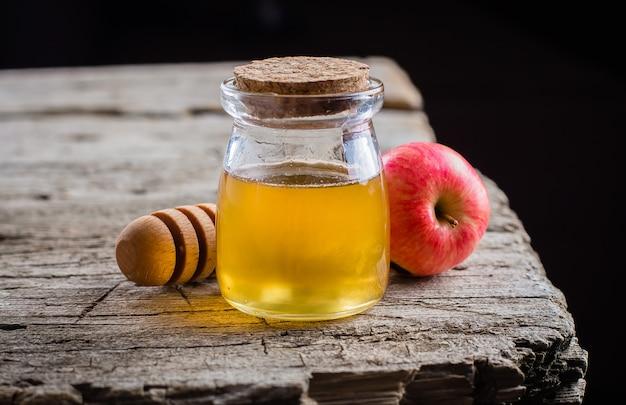 Honey jar und äpfel auf schönem behälter auf holztischhintergrund. jüdischer feiertag rosh hashanah