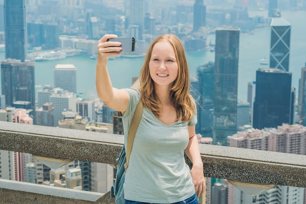 Hong kong victoria peak frau, die selfie-stickbildfoto mit smartphone nimmt, das ansicht über genießt