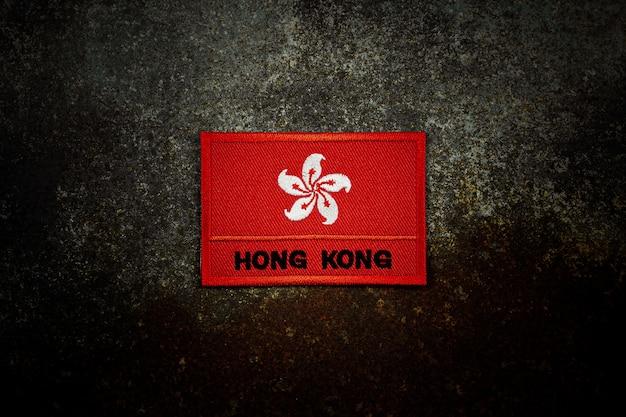 Hong- kongflagge auf rostigem verlassenem metallboden in der dunkelheit.